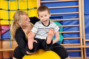 Woman As A Therapist At Physiotherapy With Medicine Ball With Child In Gym
