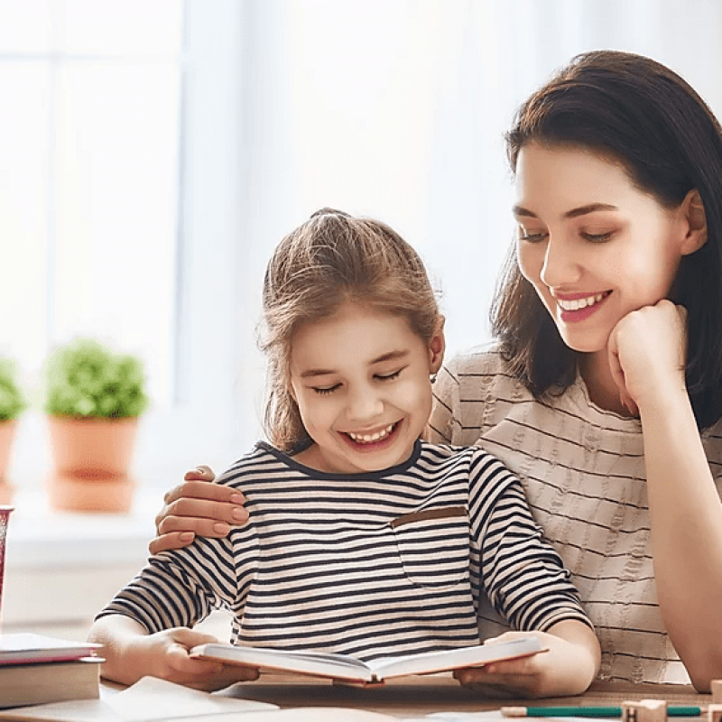Therapist working with young girl on speech articulation