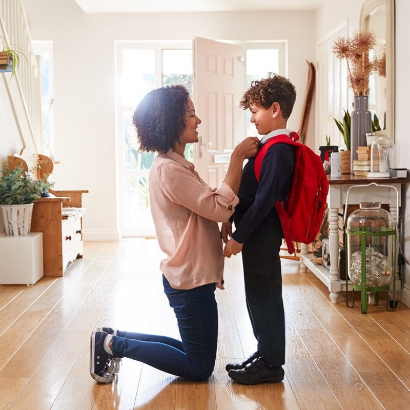 Mom kneeling at eye level with child wearing backpack